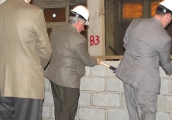 Senator Fontana, center, busts the wall to signify the beginning of construction for the Shanahan Apartments.